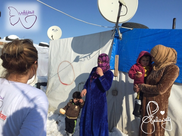 Syrian mothers trying to keep their children warm in a refugee camp